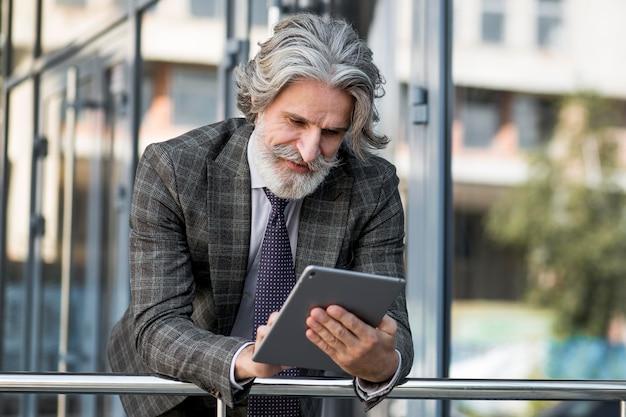 Бородатый пожилой мужчина просматривает планшет