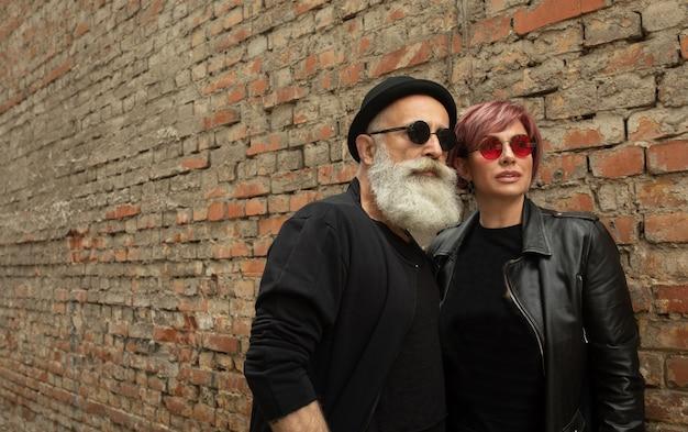 Бородатый старший мужчина и женщина носить кожаные куртки. счастливая пара пенсионеров в байкерской одежде.