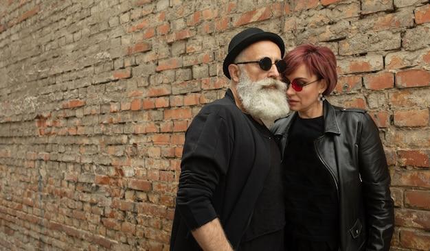 ひげを生やした年配の男性と女性の革のジャケットを着ています。バイカーの服で退職者の幸せなカップル。