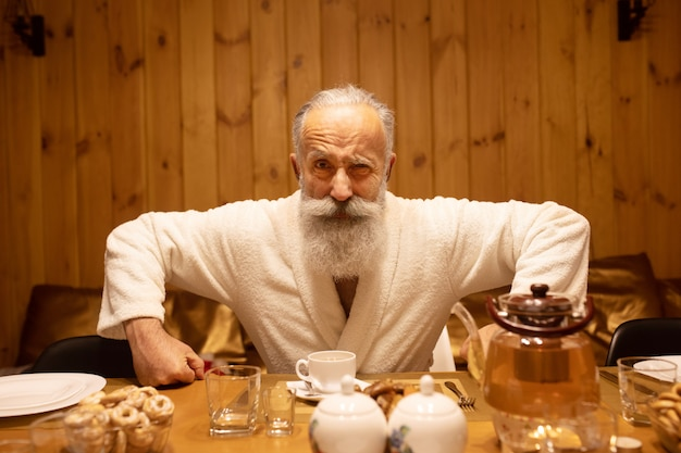 Bearded senior man drink tea after the procedure in the sauna. concept - healthy lifestyle.