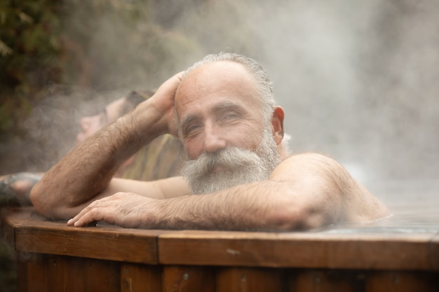タラソテラピーセンターで温泉を楽しんでいるひげを生やした年配の男性。