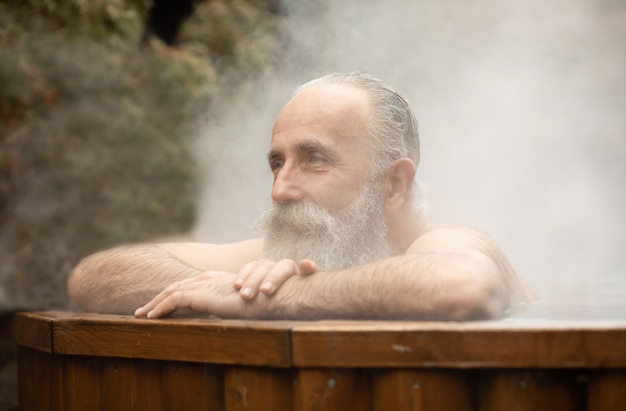Bearded senior man enjoying thermal bath in thalassotherapy center.