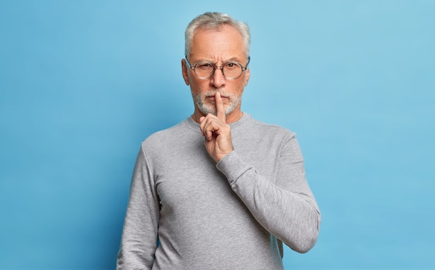 Bearded senior man has serious expression makes hush gesture asks to be quiet with finger on lips demands silence wears optical glasses and long sleeved jumper isolated on blue wall