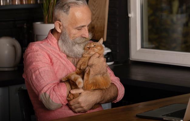 家でかわいい猫を保持しているひげを生やした年配の男性。