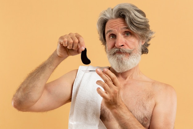 Bearded senior man holding eye patches