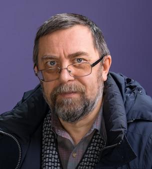 Бородатый старший мужчина в очках позирует в студии