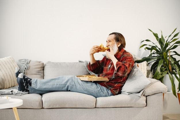 Bearded senior man lying on couch and eating pizza. fast food.