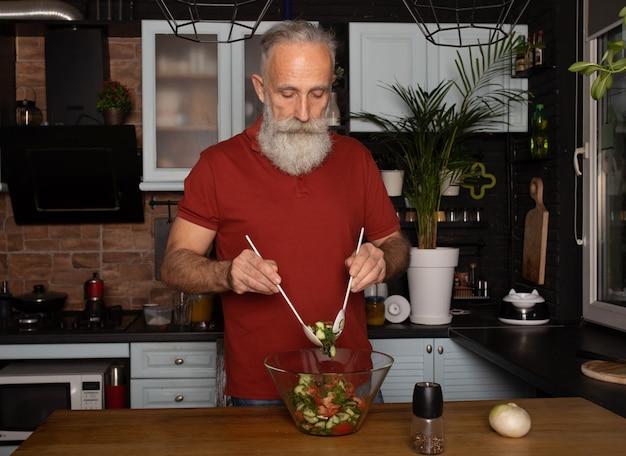 ひげを生やした年配の男性人がキッチンで健康的でおいしいサラダを準備します。