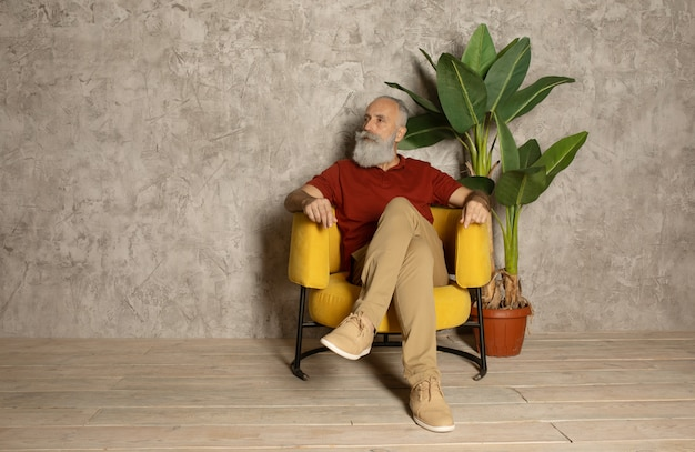 Bearded senior man relaxing in yellow armchair.