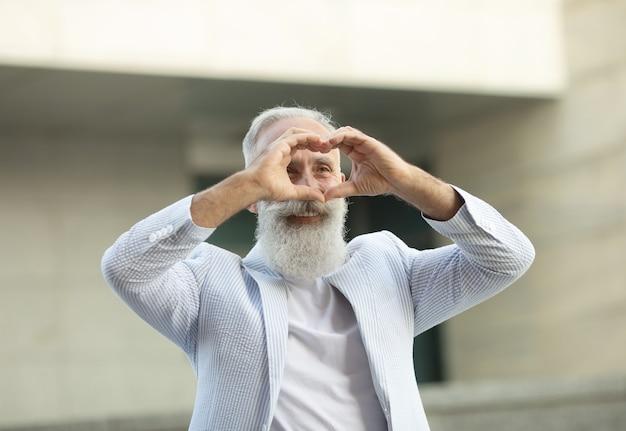Бородатый старший мужчина показывает знак любви на открытом воздухе
