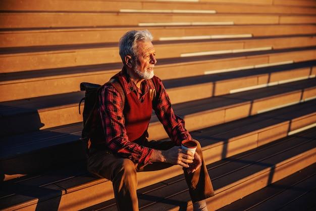 Бородатый старший мужчина сидит на лестнице на открытом воздухе, смотрит на что-то и пьет кофе с собой.
