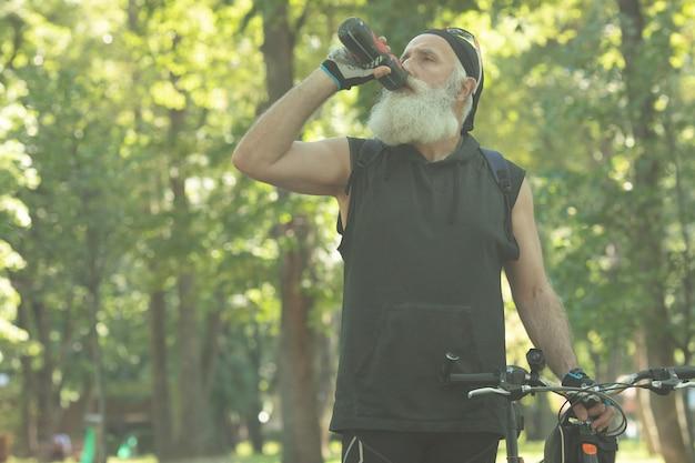 Бородатый старший мужчина с велосипедом