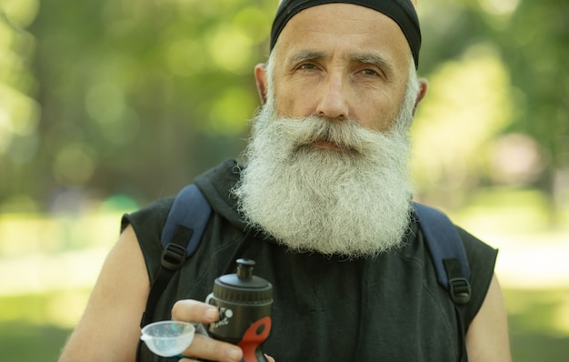 Бородатый старший мужчина с бутылкой воды