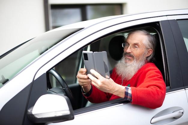 차 주차장에 앉아 있는 동안 전화를 들고 문자 메시지를 보내는 안경을 쓴 수염 난 노인