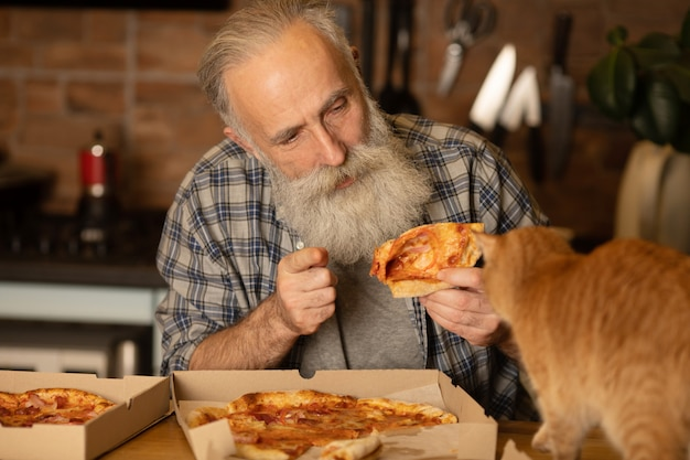 Bearded senior man with his red cat eating pizza at home kitchen.