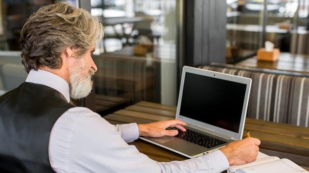 Uomo maggiore barbuto che lavora al computer portatile