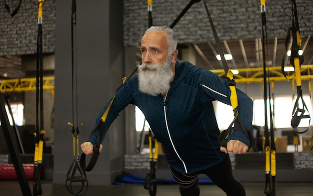 ジムでtrx抵抗バンドを使ってトレーニングのひげを生やした上級スポーツマン。