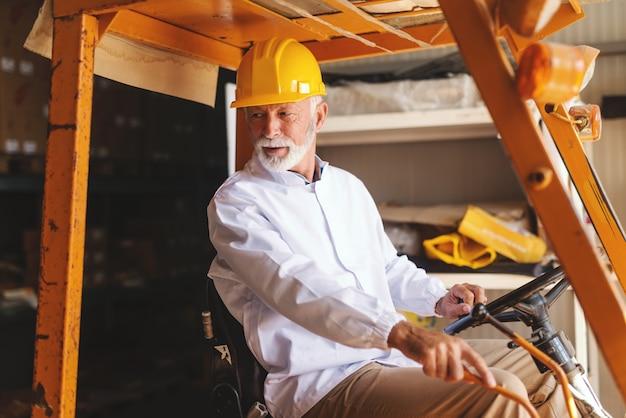 Бородатый старший работник в форме и с защитным шлемом на голове управляя грузоподъемником в хранении.