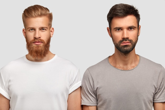 Bearded serious man friends with trendy haircut, stand close to each other, think where spend free time