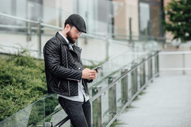 Un uomo barbuto, serio ed elegante in piedi per le strade della città vicino a un moderno centro uffici con un telefono cellulare