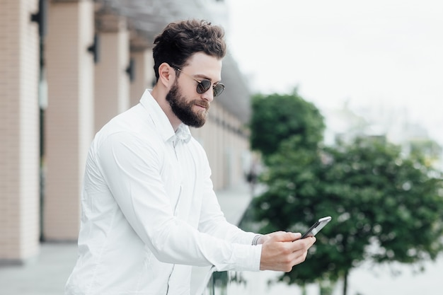 A bearded, serious, stylish man in white shirt and sunglasses standing on the streets of the city and surfing smartphone