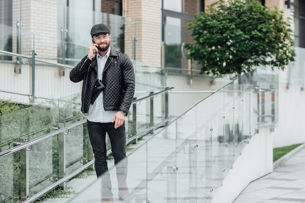A bearded, serious, stylish manager speaking phone on the streets of the city near modern office