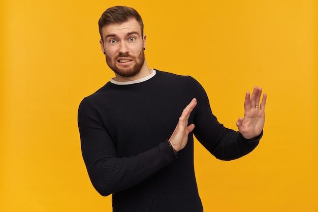 Шокированный бородатый парень, скептически настроенный мужчина с брюнетками. имеет пирсинг. в черном свитере. отталкивает руки, отвергает жест. изолированные над желтой стеной