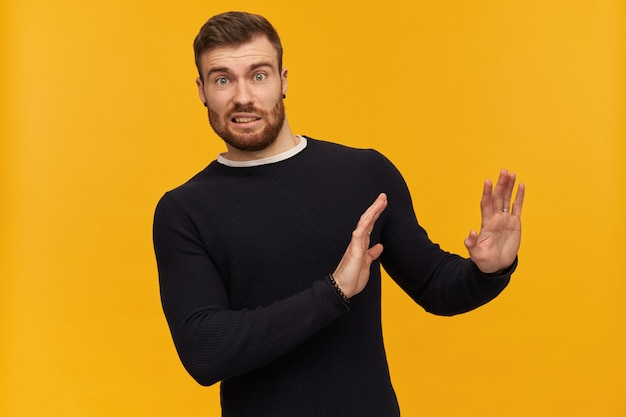 Bearded shocked guy, skeptical looking man with brunette hair. has piercing. wearing black sweater. pushes arms away, reject gesture.  isolated over yellow wall