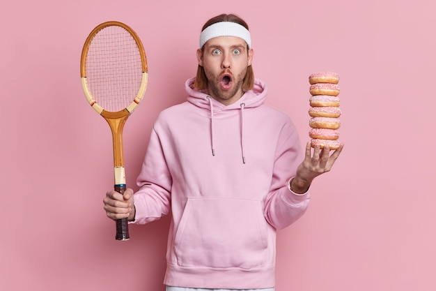 Bearded shocked hipster wears sport outfit holds tennis racket and pile of sweet doughnuts gazes surprisingly with widely opened mouth has active leisure.