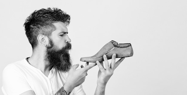 Bearded shoemaker. bearded man holding last shoe. serious young cobbler sets up business. shoemaker holding wooden footwear.