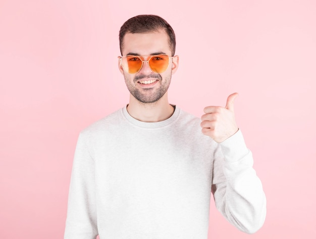Bearded shows sign super with fingers, man in love wears glasses in the shape of a heart, portrait, pink wall