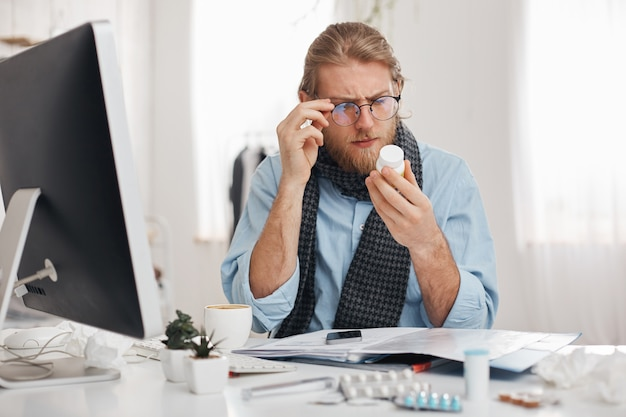 Bearded sick male office worker with spectacles on reads prescription of medicine. young manager has bad cold, sits at table with pills, tablets, vitamins and drugs on its surface. health problems