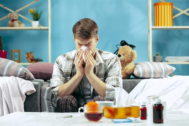독감 집에서 소파에 앉아 그의 코를 불고 수염 된 아픈 남자. 겨울, 질병, 인플루엔자, 통증 개념. 집에서의 휴식. 의료 개념.
