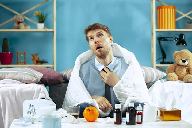 Бородатый больной человек с гриппом сидит на диване у себя дома и пьет чай. зима, болезнь, грипп, понятие боли. отдых дома. концепции здравоохранения.