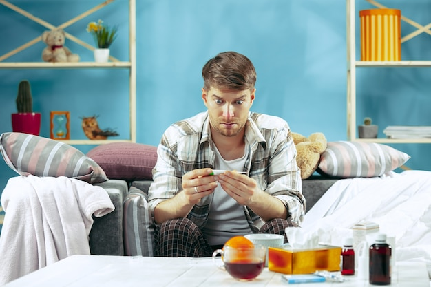 독감 집에서 소파에 앉아 체온을 측정 수염 아픈 남자. 겨울, 질병, 인플루엔자, 통증 개념. 집에서의 휴식