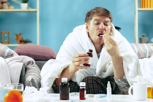 독감이 집에서 소파에 앉아 따뜻한 담요로 덮여 있고 기침에서 시럽을 마시는 수염 난 아픈 남자. 질병, 인플루엔자, 통증 개념. 집에서의 휴식