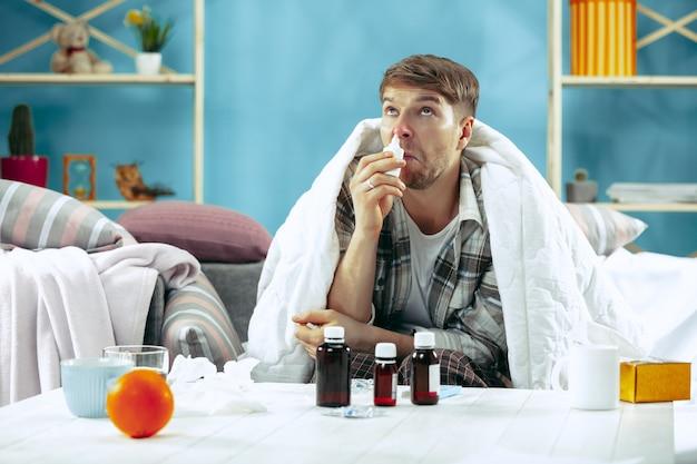 독감이 집에서 소파에 앉아 따뜻한 담요로 덮여 비강 스프레이를 사용하는 수염 난 아픈 남자. 질병, 인플루엔자, 통증 개념. 집에서의 휴식