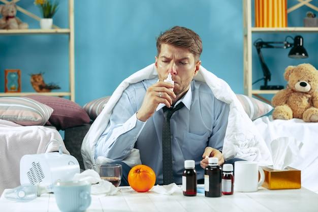 Uomo barbuto malato con canna fumaria seduto sul divano a casa coperto con una coperta calda e utilizzando spray nasale. la malattia, l'influenza, il concetto di dolore. relax a casa
