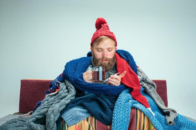 Uomo barbuto malato con canna fumaria seduto sul divano a casa o in studio con una tazza di tè ricoperta di vestiti caldi lavorati a maglia. malattia, concetto di influenza. relax a casa. concetti sanitari.