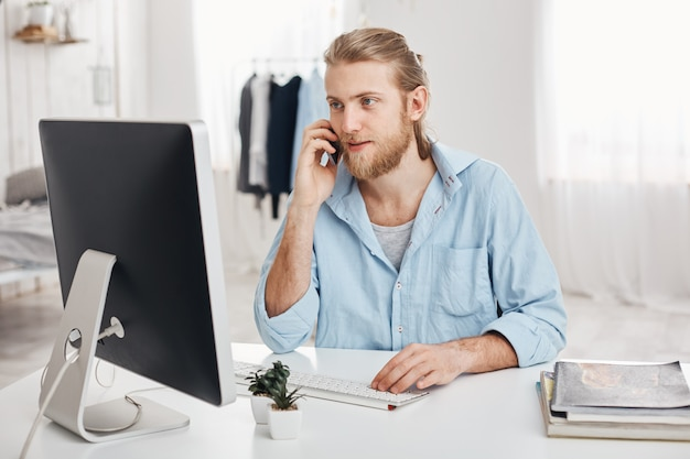 Bearded skilled young fair-haired businessman works on new project, sits in front of screen, has phone conversation, discusses financial report with businesspartner. office worker chats with boss