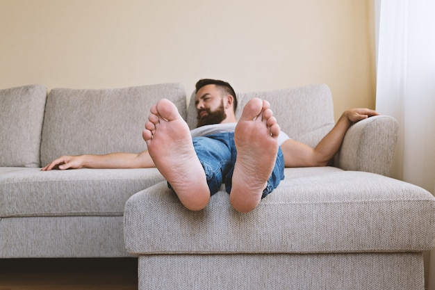 Bearded sleeping hipster on beige sofa