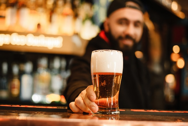 Bearded and smiling barman gives beer
