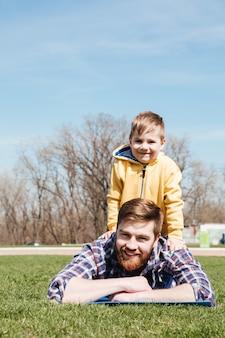 Бородатый улыбающийся отец лежит с маленьким сыном в парке.