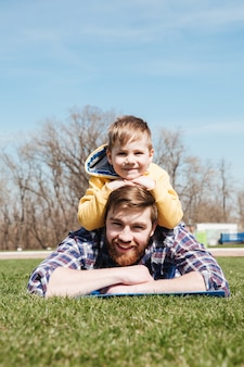 Bearded smiling father lies with little son in the park.