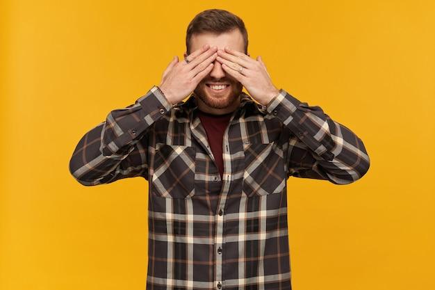 ひげを生やした笑顔の男、ブルネットの髪の幸せそうな男。市松模様のシャツとアクセサリーを身に着けています。手のひらで目を閉じます。かくれんぼ。黄色い壁の上に隔離されたスタンド
