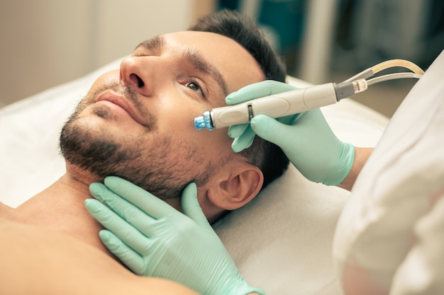 Бородатый улыбающийся мужчина, лежащий на подушке, и руки косметолога в резиновых перчатках, держа в руках современный инструмент для питания кожи