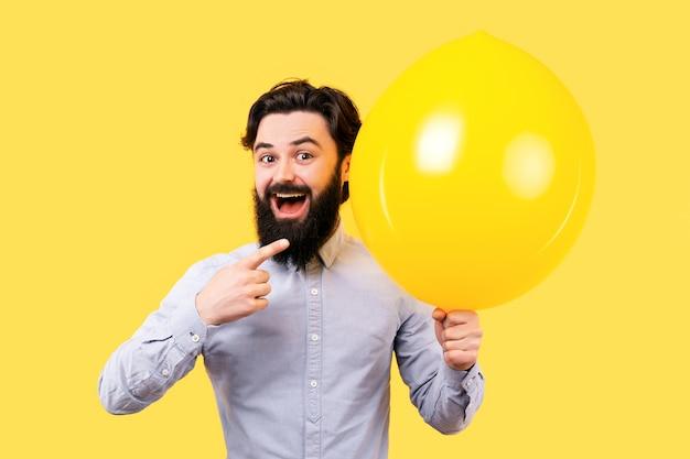黄色い風船を指しているひげを生やした笑顔の男