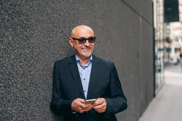 Bearded smiling senior adult standing against the wall outdoors and using smart phone.