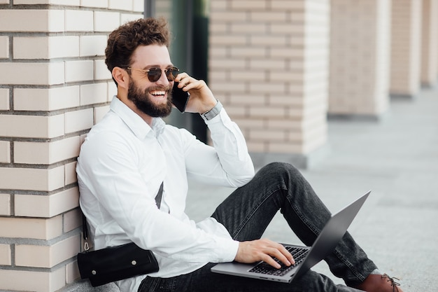 A bearded, smiling, stylish man sitting on the flour on the streets of the city near modern office centre and workin with his laptop and calling phone