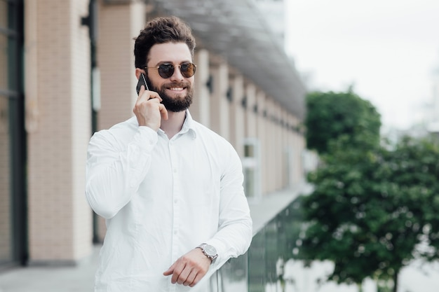 A bearded, smiling, stylish man in white shirt and sunglasses standing on the streets of the city and calling on mobile phone